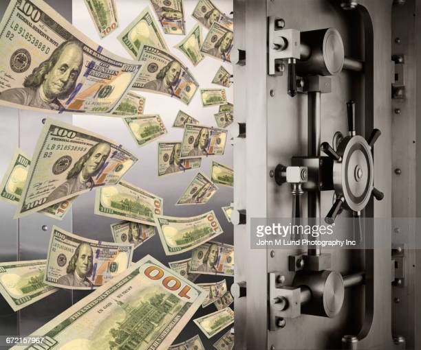 Money flowing from open vault door