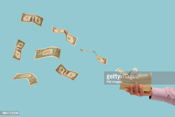 money flying off stack of bills in man's hand - in de lucht zwevend stockfoto's en -beelden