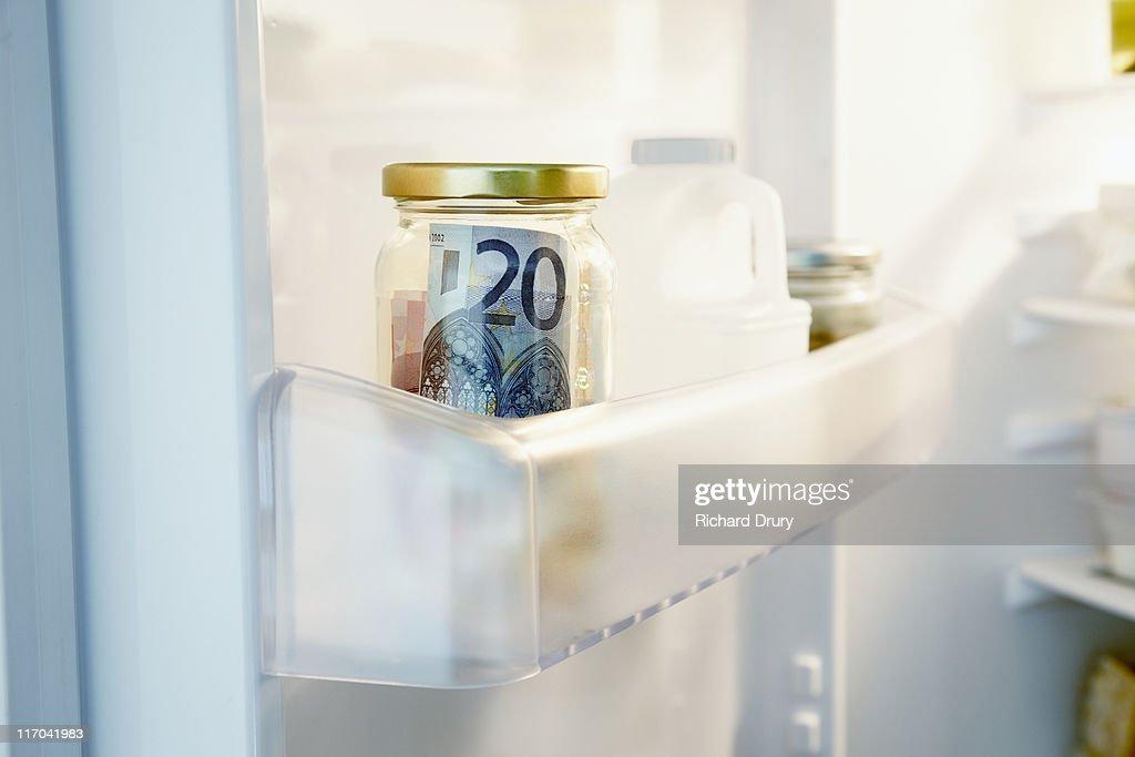 Money hidden in jar in fridge : Stock Photo