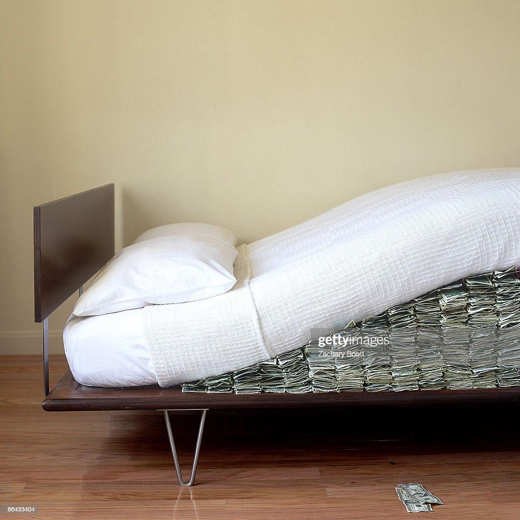 Money hidden under Modern bed mattress : Stock Photo