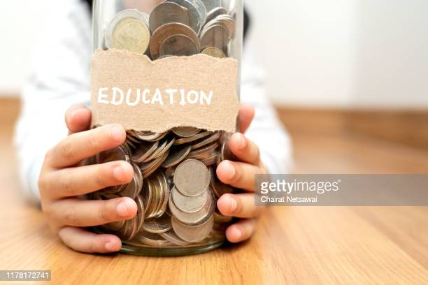 money in children's hands.happy asian boy holding glass bottle and saving money into glass bottle.education and concept. - stipendium stock-fotos und bilder