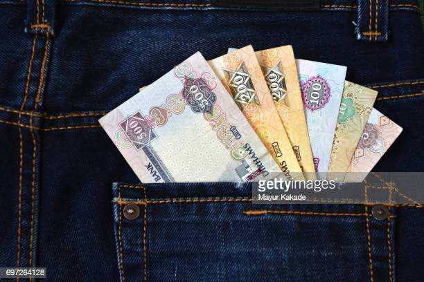 money in jeans back pocket - gulf countries stock pictures, royalty-free photos & images