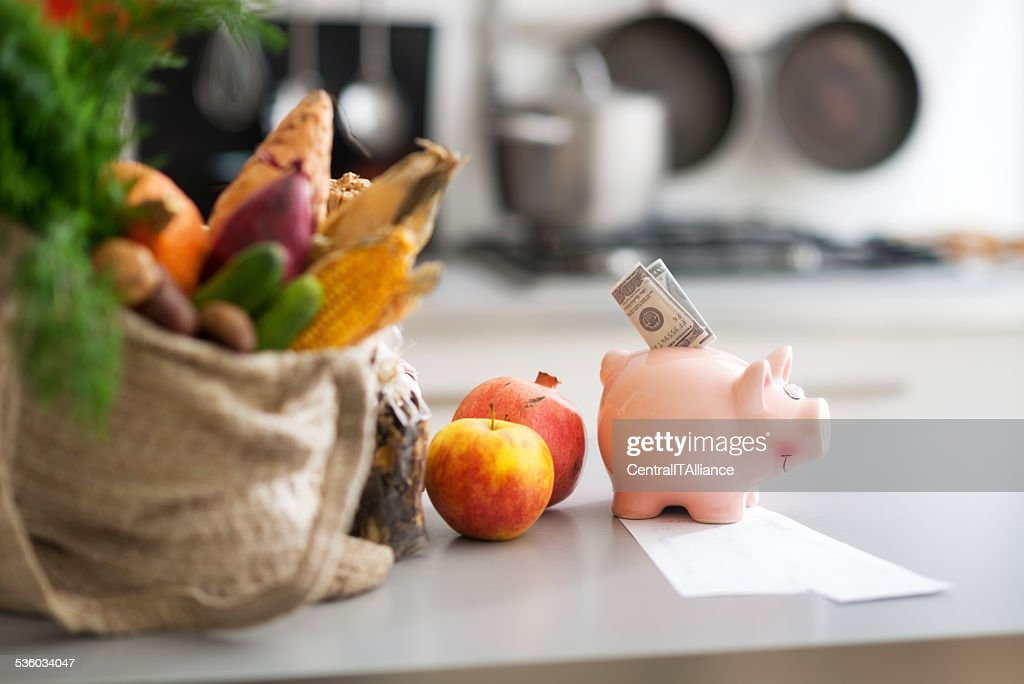 Money in piggy bank and purchases on table. Closeup : Stock Photo