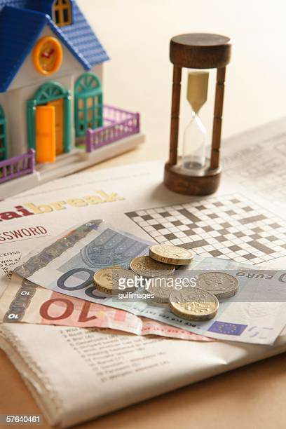 Money on the newspaper with Doll House and Hourglass
