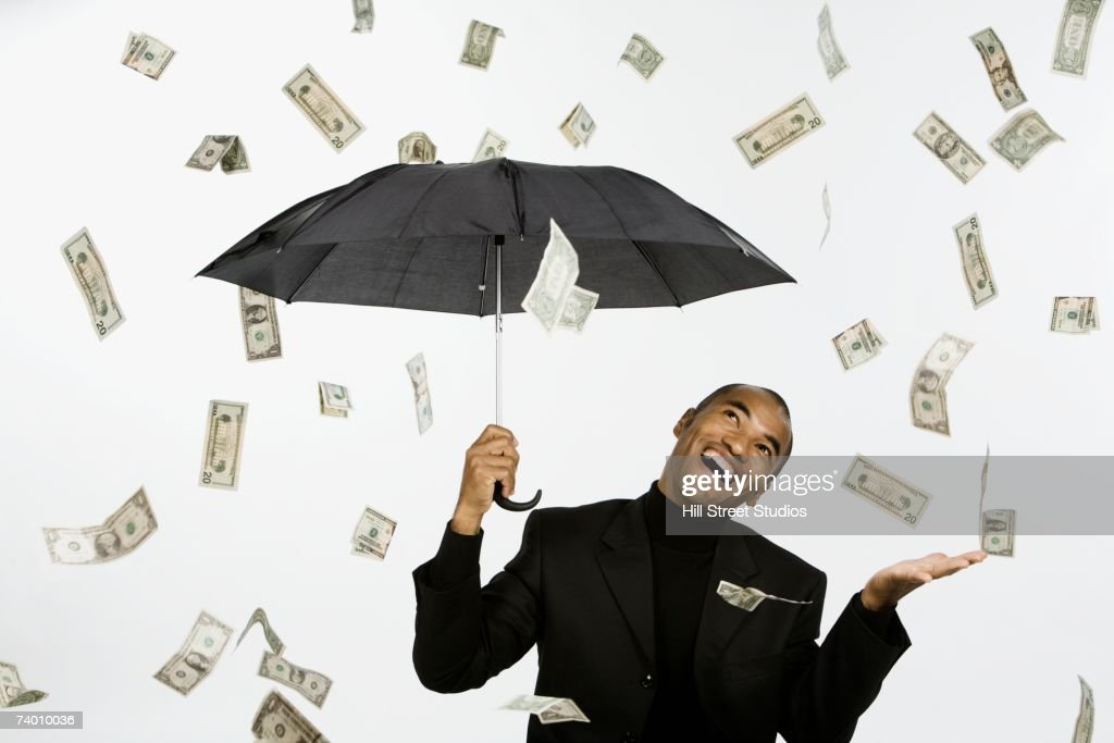 Money Raining Down On Asian Businessman Under Umbrella Stock Photo