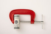 Money roll clamped in a red clamp on a white background