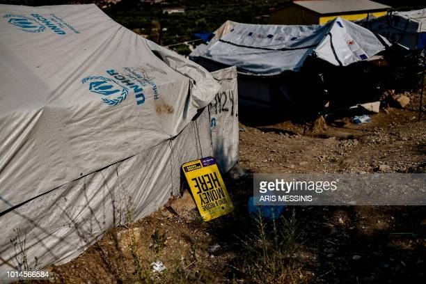 A money transfer placard is placed outside a tent at a camp next to the Moria refugee camp in the island of Lesbos on August 5 2018
