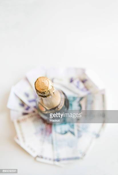 Money under bottle of champagne