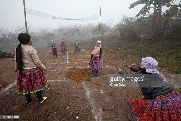 H'mong girls in nice traditional dress playing traditional game throwing a ball through the net in Moc Chau Farm Town during the H'mong New Year...