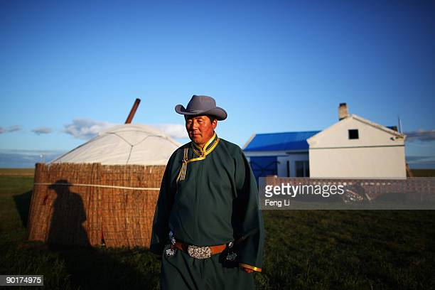 Mongol herdsman named Gegenhasi stands in front of his new house to welcome guests in the Huhenuoer Grassland on August 27 2009 in Hulun Buir Inner...