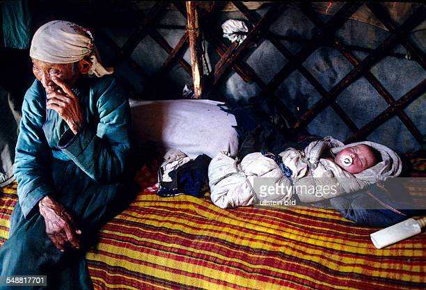 MNG Mongolia a grandmother watching her grandchild who is wrapped tightly in blanket Province of Khoevsgoel