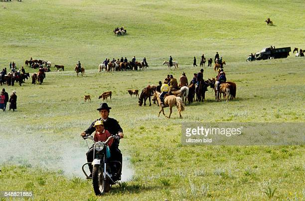 Mongolia, a motorcycle and many horses at the annual Naadam festival in Tsertserleg, Arhangay province.