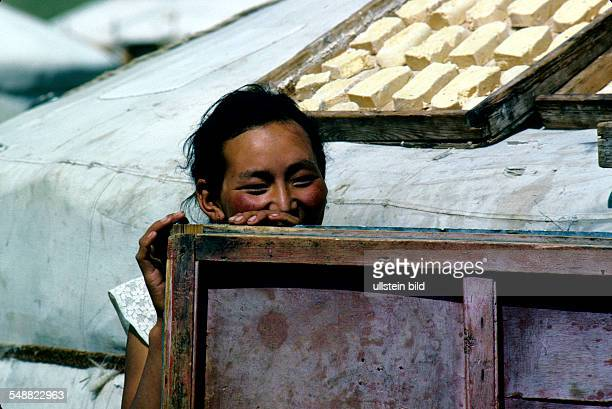 Mongolia, a shy young nomad women hiding behind her door of the Jurt lies camel cheese to he dried. Gobi steppe, Oevoer-Hangay province.