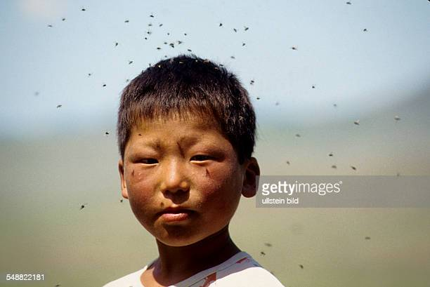 Mongolia, boy with a swarm of flies in the Bulgan province.