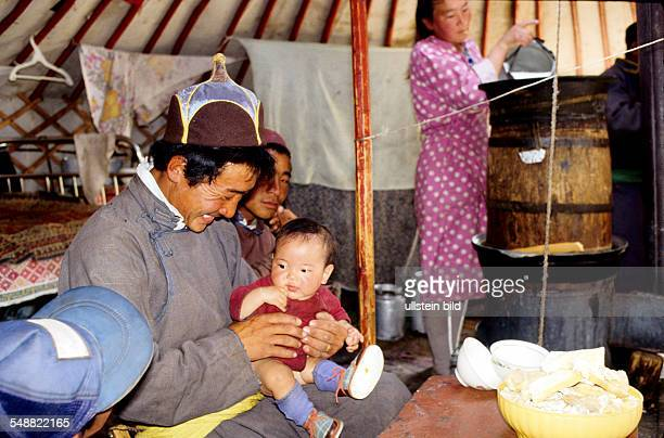 MNG Mongolia family life in a Jurt in the Khoevsgoel province The father is playing with his child while the mother is preparing Oeroem