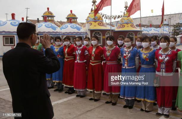 Mongolian and Chinese waitresses wearing Mongolian costumes line up for a pep talk from their boss in front of traditional Mongolian Yurts at the...