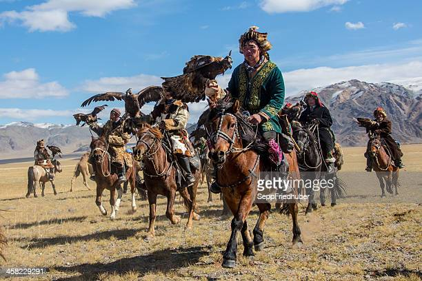 mongolian eagle hunters riding to the festival. - independent mongolia stock pictures, royalty-free photos & images