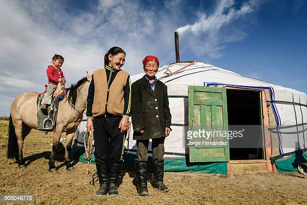 Mongolian family posing for the camera outside their yurt