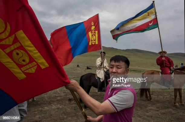 Mongolian followers of Shamanis or Buu Murgal carry flags before a fire ritual meant to summon spirits to mark the period of the Summer Solstice on...