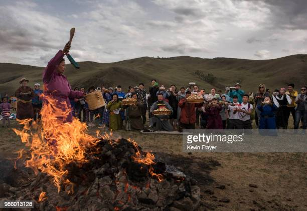 Mongolian followers of Shamanism or Buu murgul pray during a blessing as part of a Zugel ritual ceremony in the grasslands on June 21 2018 outside...