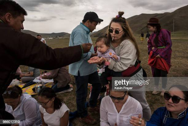 Mongolian followers of Shamanism or Buu murgul takes rice as a blessing during a ceremony in the grasslands on June 21 2018 outside Ulaanbaatar...