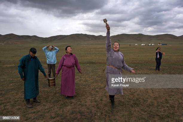 Mongolian followers of Shamanism or Buu murgul throw milk during a blessing as part of a Zugel ritual ceremony in the grasslands on June 21 2018...