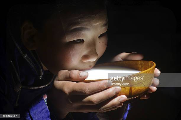 Mongolian girl drinking milk from a bowl
