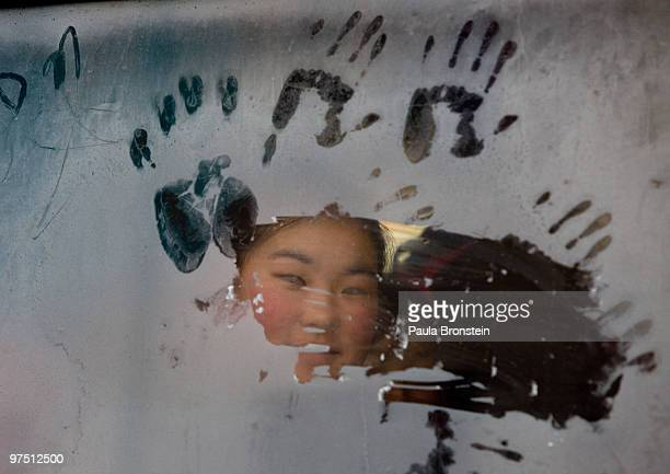 Mongolian girl looks out from a frosty window riding on a city bus March 6 2010 in Ulaan Baatar Mongolia Monglia is still experiencing one of the...