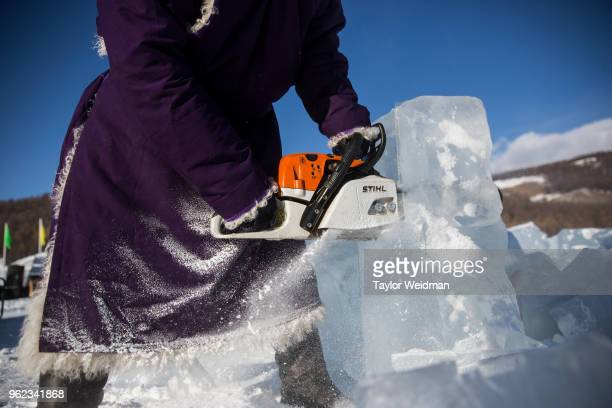 Mongolian man cuts blocks of ice with a chainsaw at the Lake Khovsgol Ice Festival in Khatgal Mongolia