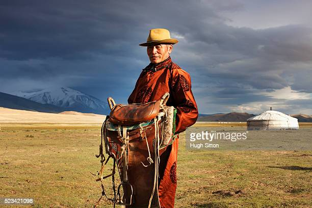 mongolian man holding a saddle - hugh sitton stock pictures, royalty-free photos & images