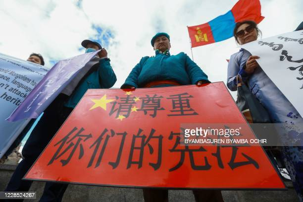 A Mongolian man holds a protest banner in the shape of the Chinese flag which reads Respect your constitution during a protest against China's plan...