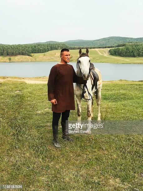 Mongolian Man horseback rider posing with his horse