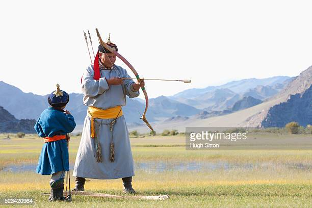 mongolian man teaching a boy how to shoot an arrow - hugh sitton stockfoto's en -beelden