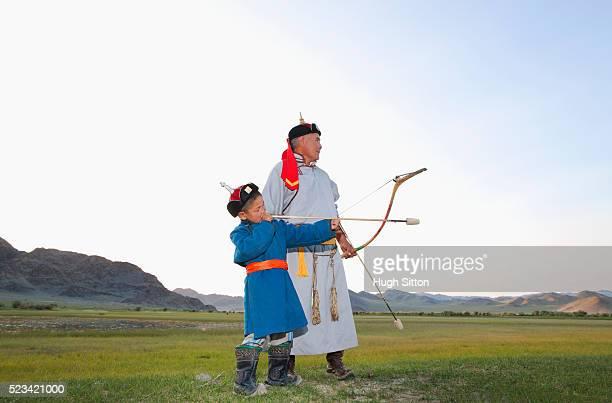 Mongolian man teaching a boy to shoot an arrow