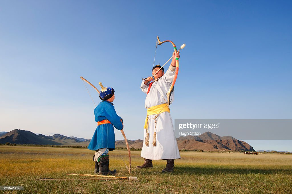 Mongolian man teaching a boy to shoot arrows : Stock Photo