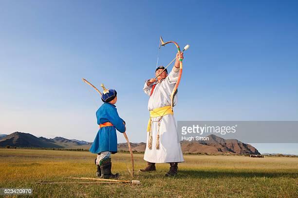 mongolian man teaching a boy to shoot arrows - hugh sitton photos et images de collection