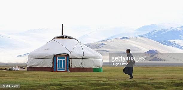 mongolian man walking towards a yurt - hugh sitton stock pictures, royalty-free photos & images