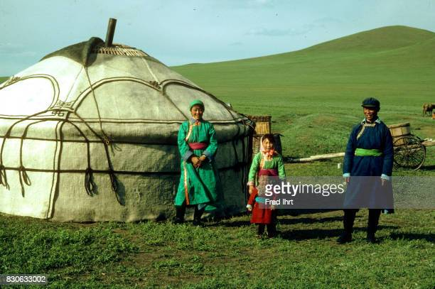 Mongolian nomad family standing in front of their yurt in the grassland