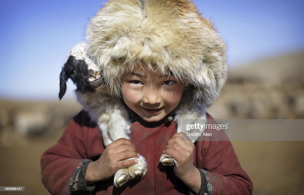 A cute Mongolian nomadic boy wearing a large fur hat carries a lamb on his shoulders. Pictured in mid winter, this nomadic family lives on the northern edge of the Gobi desert in the foothills of the Gobi Altai Mountains (Govi Altai Nuruu) around the area of Khongoryn Els (The Singing Sands, Singing Dunes), Gobi Gurvansaikhan National Park, Ömnögovi Province, Southern Mongolia
