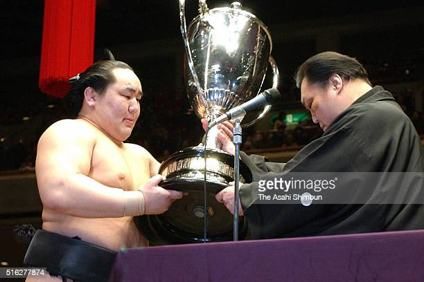 Mongolian ozeki Asashoryu receives the trophy from the Japan Sumo Association President stable master Kitanoumi after winning the tournament during...