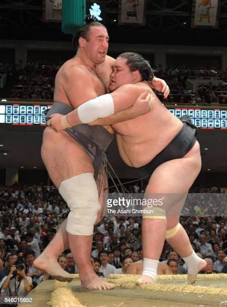 Mongolian ozeki Terunofuji pushes Georgian wrestler Tochinoshin out of the ring to win during day three of the Grand Sumo Autumn Tournament at...