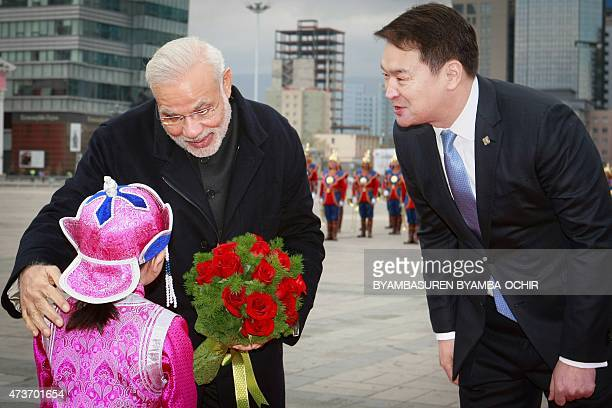 Mongolian Prime Minister Chimed Saikhanbileg looks on as India's Prime Minister Narendra Modi receives a bouquet of flowers from a Mongolian child...