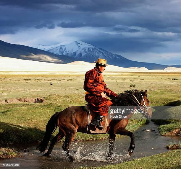 mongolian riding a horse - hugh sitton stock-fotos und bilder