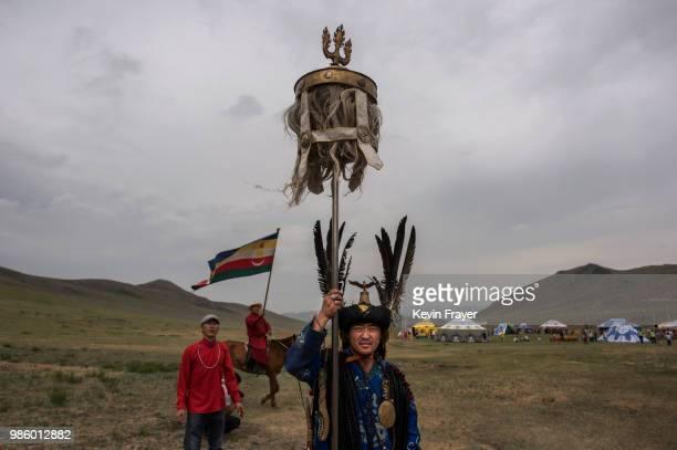 Mongolian Shaman or Buu carries a banner from the period of Chinggis Khan before a fire ritual meant to summon spirits to mark the period of the...