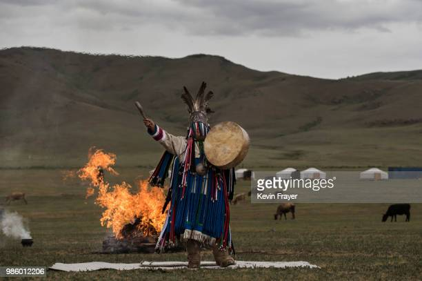 Mongolian Shaman or Buu gestures during a fire ritual during a ceremony in the grasslands on June 21 2018 outside Ulaanbaatar Mongolia Banned for 70...