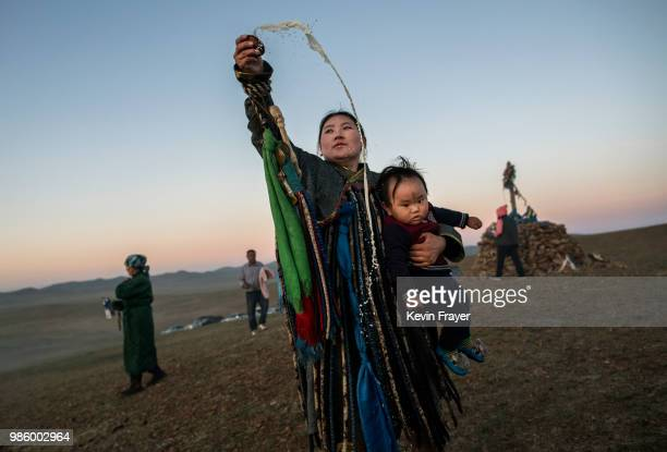 Mongolian Shaman or Buu holds her child while throwing milk as an offering during a sun ritual ceremony to mark the period of the Summer Solstice in...