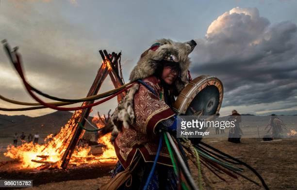 Mongolian Shamaness or Buu beats her drum while taking part with others in a fire ritual meant to summon spirits to mark the period of the Summer...