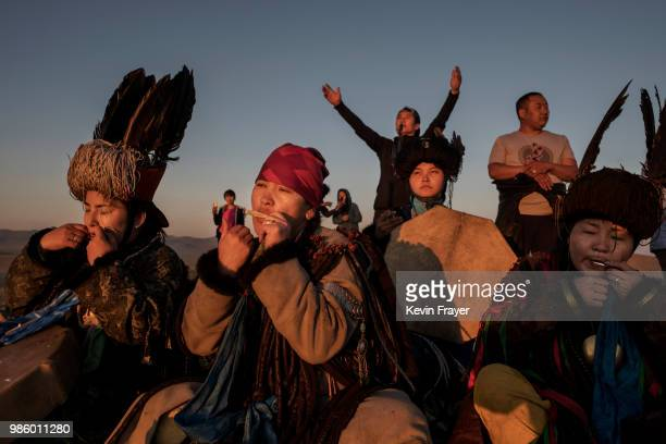 Mongolian Shamans or Buu play the south harp as they sit together while taking part in a sun ritual ceremony to mark the period of the Summer...