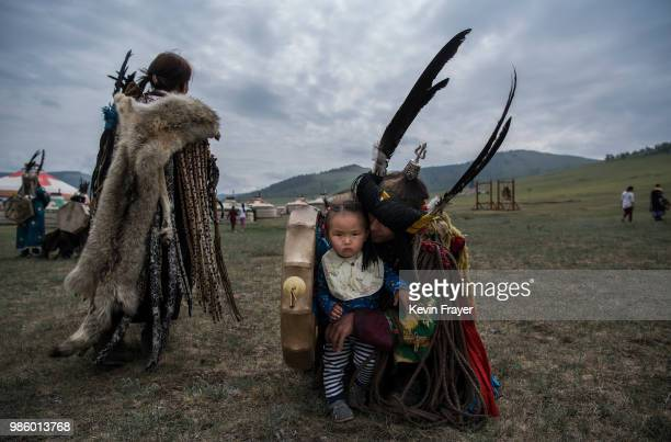 Mongolian Shamans or Buu sits with his child before a fire ritual meant to summon spirits to mark the period of the Summer Solstice June 23 2018...