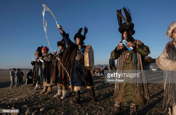 Mongolian Shamans or Buu throw milk as an offering during a sun ritual ceremony to mark the period of the Summer Solstice in the grasslands at...